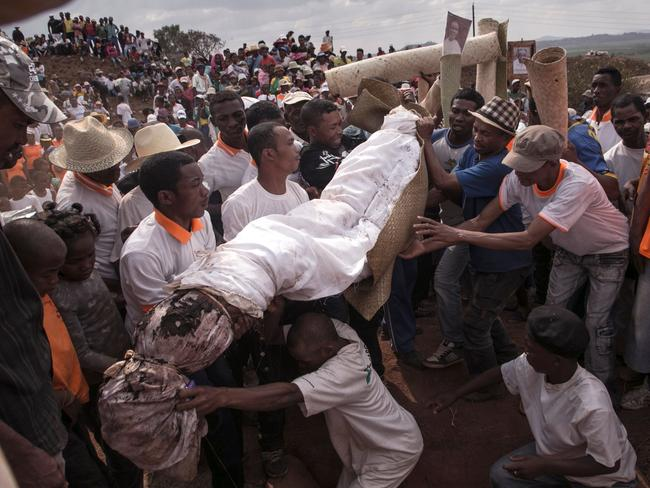 People carry a body wrapped in a sheet as they take part in the Famadihana in the village of Ambohijafy, a few kilometres from Antananarivo, in Madagascar on September 23. Picture: AFP/RIJASOLO