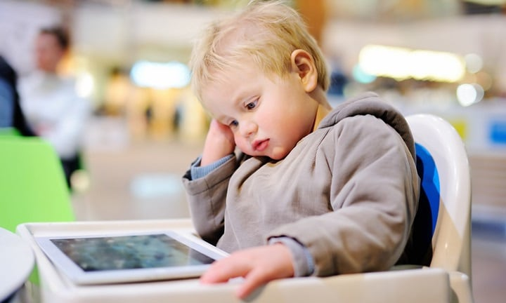 Bored blonde toddler boy with a digital tablet indoors