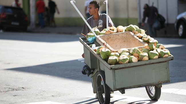 A man carts coconuts for sale on a street in downtown Sao Paulo, Brazil. Coconut water can be extracted and drank after a young coconut is cut open. Picture: Bloomberg