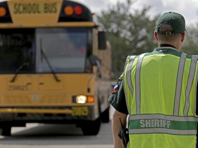 A deputy with the Broward County Sheriff's Office directs traffic outside of Marjory Stoneman Douglas High School in Parkland. Picture: AP