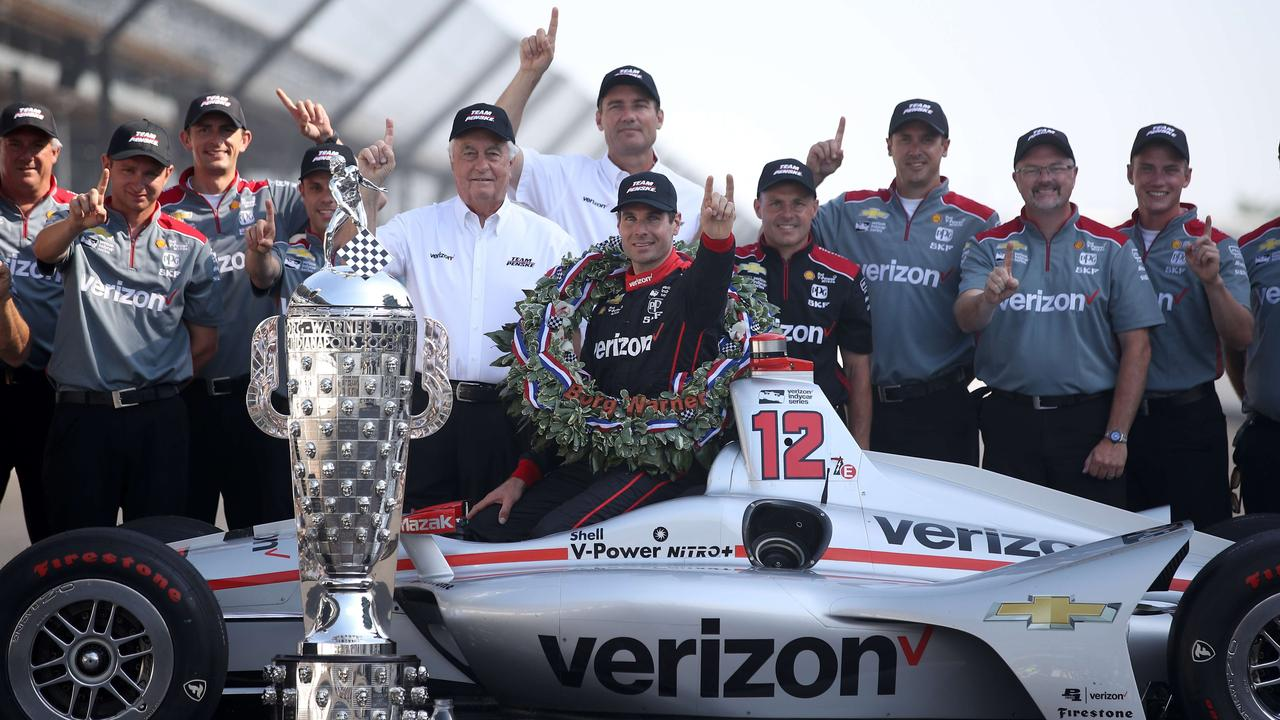 Power with team bosses Roger Penske and Tim Cindric, plus the crew of his No. 12 car.