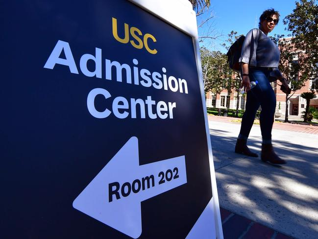 A woman walks past a sign directing people toward USC's Admission Center at the University of Southern California (USC) in Los Angeles, California. Picture: AFP