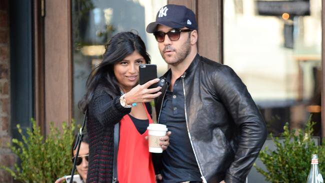 Ladies man Jeremy Piven stops for selfies with a female fan in New York.
