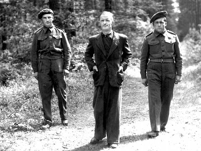 "William Joyce, aka Lord Haw Haw, centre, with two guards while under arrest in Germany in 1945. Joyce named the Allies the ""Rats of Tobruk""."