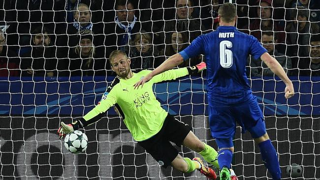 Leicester City's Danish goalkeeper Kasper Schmeichel (L) dives to save a shot.