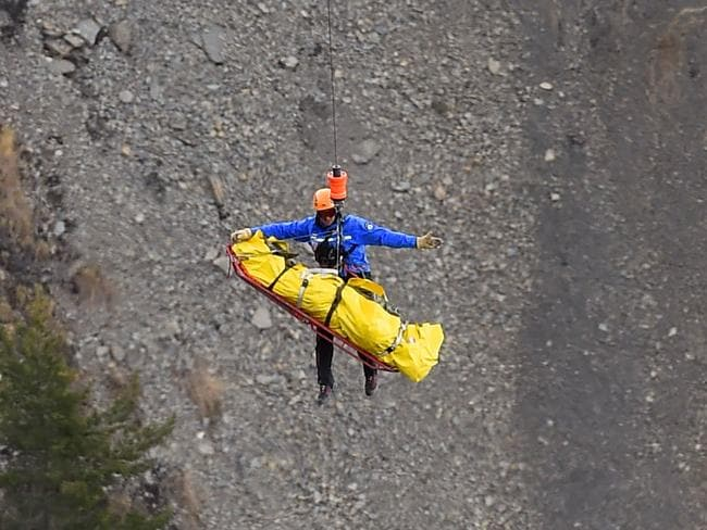Retrieval ... Rescue workers retrieve bodies from the crash. Picture: AFP/ ANNE-CHRISTINE POUJOULAT