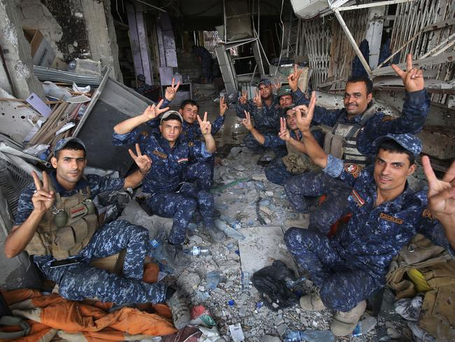 Members of the Iraqi federal police flash the sign for victory after driving IS out of the Mosul Old City. Picture: AFP PHOTO / AHMAD AL-RUBAYE