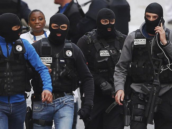 Protection ... hooded police officers walk in a street of Saint-Denis, near Paris. Picture: AP Photo/Peter Dejong