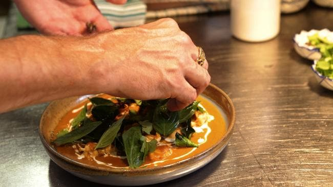 Chef Ben Bertei plates the coconut and turmeric curry of Moreton Bay bug, Asian celery and Kaffir lime, at LongTime, Fortitude Valley. Picture: Anthony Weate