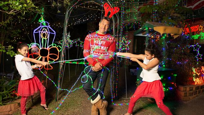 Jamie Durie gets all wrapped up in Christmas lights with sisters Sophia and Sara. Picture: Allianz Australia/ Matthew Reed