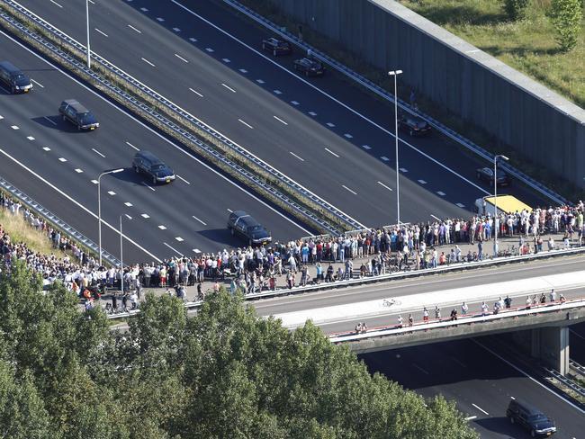 Massive loss ... hundreds of people gather on a bridge to observe a convoy of hearses containing the victims of the downed flight MH17, driving from the Eindhoven Airbase to Hilversum. Picture: Jerry Lampen