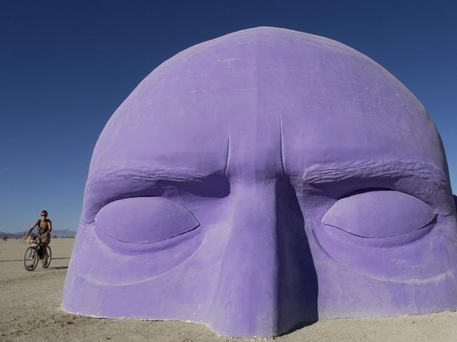 A giant head, one of many art installations dotting the playa at Burning Man, appears to emerge from the sand at the 2005 festival. Picture: Jim Rankin/The Toronto Star/Getty Images