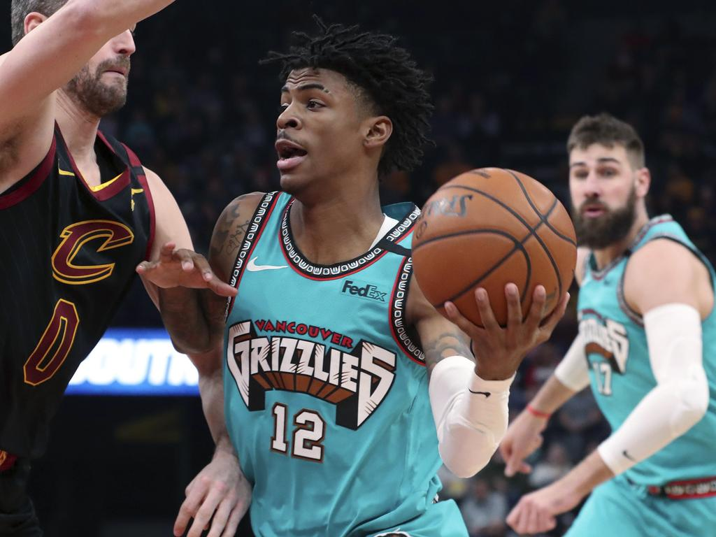 Memphis Grizzlies guard Ja Morant (12) looks to pass the ball as Cleveland Cavaliers forward Kevin Love (0) defends during the first half of an NBA basketball game Friday, Jan. 17, 2020, in Memphis, Tenn. (AP Photo/Karen Pulfer Focht)