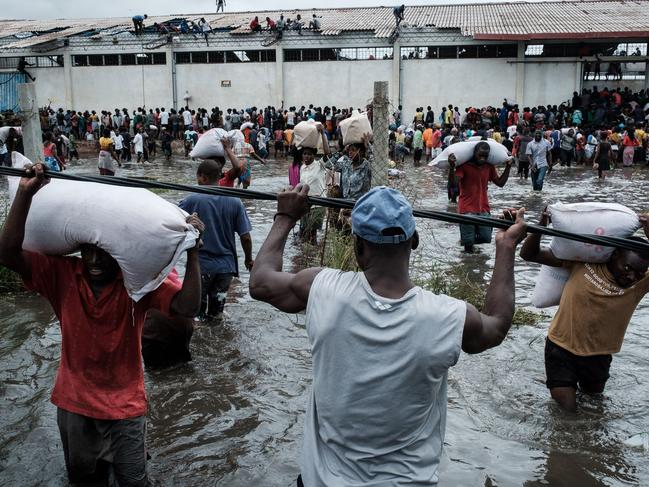 People take part in the looting sacks of Chinese rice from a warehouse which is surrounded by water after cyclone hit in Beira, Mozambique. Picture: AFP