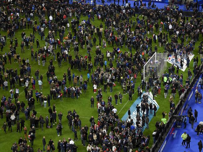Football fans gather in the field as they wait for security clearance to leave the Stade de France. AFP/Frank Fif.