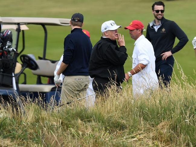 President Donald Trump talks as his son Eric Trump waits as they play golf at Trump Turnberry Luxury Collection Resort during the President's first official visit to the United Kingdom last year. Picture: Getty