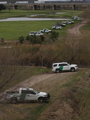 "Law enforcement and Border Patrol vehicles line the river Eagle Pass in a US ""show of force"" against migrants. Picture: Joe Raedle"