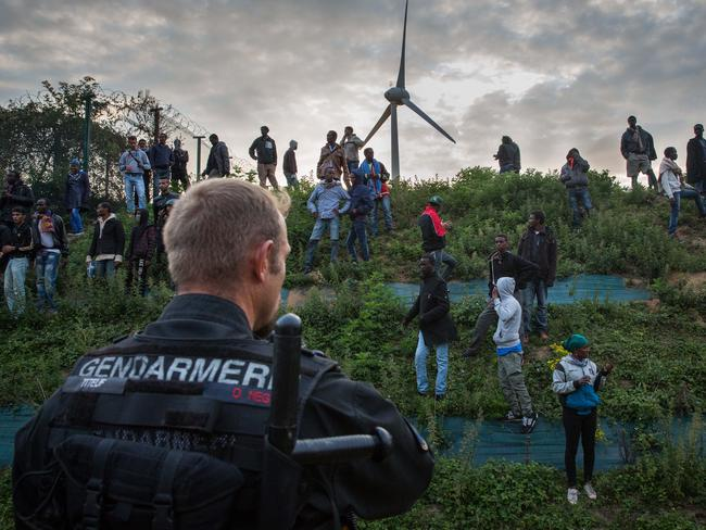 Tense stand-off ... a Gendarme watches as the migrants wait for their next run. Picture: Rob Stothard/Getty Images
