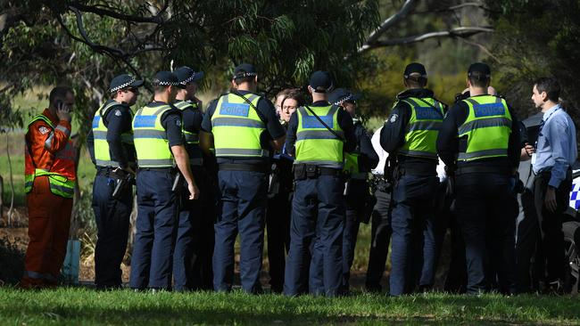 Police are seen at a staging point in Royal Park, Melbourne, after a woman's body was found at Parkville. Picture: AAP Image/James Ross.