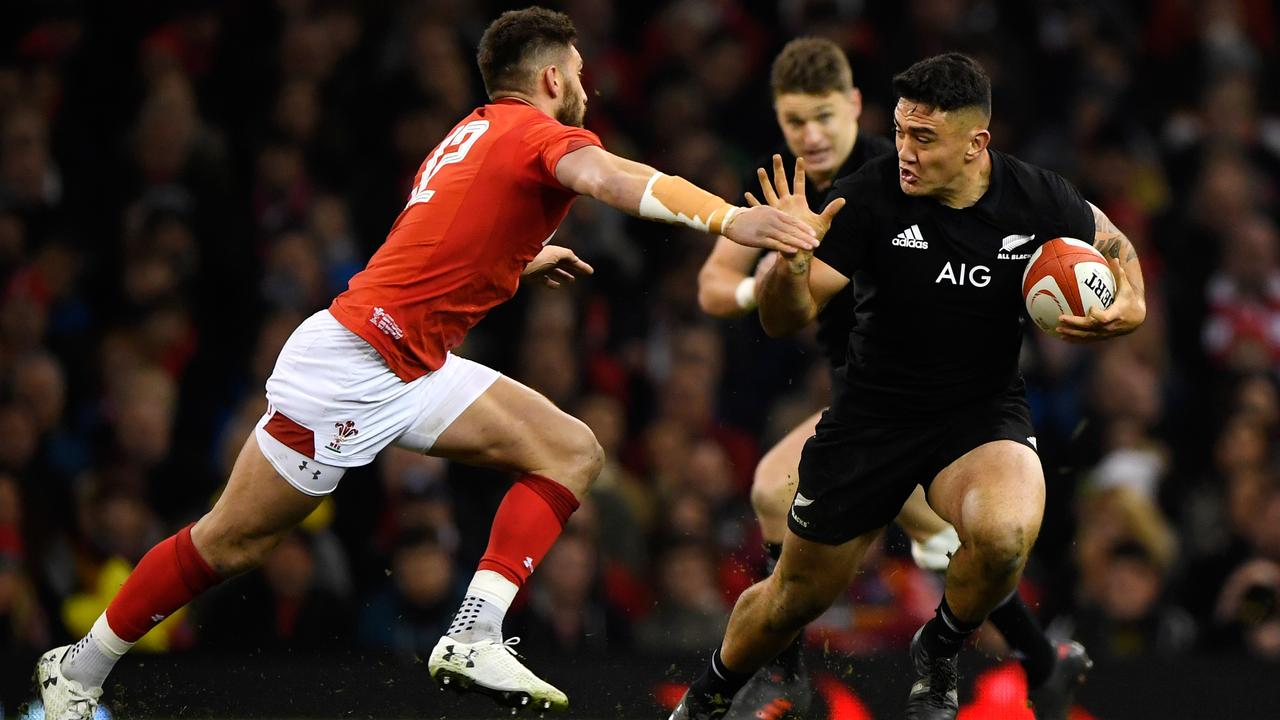 Codie Taylor of New Zealand escapes the tackle of Owen Williams of Wales.