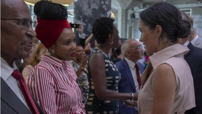 Meghan meets Nelson Mandela's granddaughter Zamaswazi Dlamini-Mandela (in red, centre) during her visit to the exhibition. Picture: Arthur Edwards — WPA Pool/Getty Images Source:Getty Images