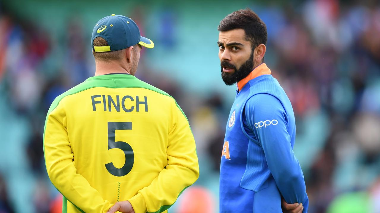 India's captain Virat Kohli gives Aaron Finch a talking-to (Photo by Adrian DENNIS / AFP)