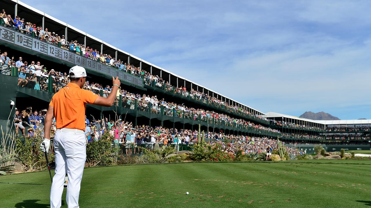 Rickie Fowler encourages the crowd before his tee shot.