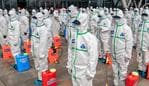 TOPSHOT - Staff members line up at attention as they prepare to spray disinfectant at Wuhan Railway Station in Wuhan in China's central Hubei province on March 24, 2020. - China announced on March 24 that a lockdown would be lifted on more than 50 million people in central Hubei province where the COVID-19 coronavirus first emerged late last year. (Photo by STR / AFP) / China OUT