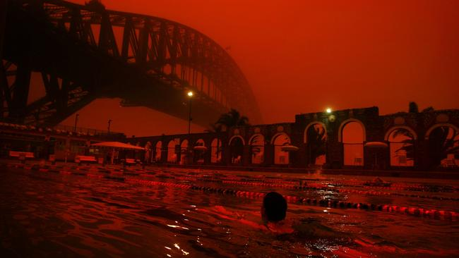 23/09/2009 NEWS: Swimmers take an early morning swim at North Sydney Pool, as a red haze blankets Sydney from a dust storm created by overnight inland winds.