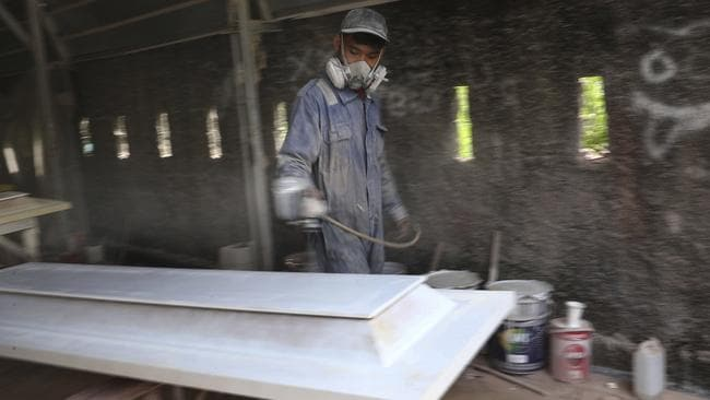 A worker at a factory outside Jakarta prepares coffins for COVID-19 victims. Picture: AP