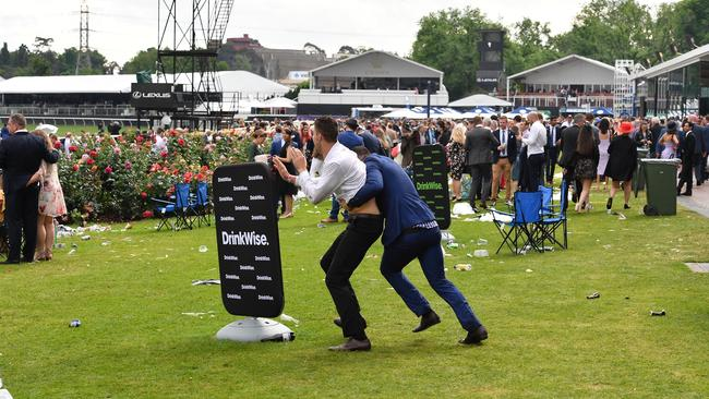 Two men tussle on the lawn. Picture: Jason Edwards