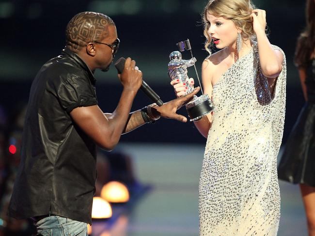 """Kanye West (L) jumps onstage after Taylor Swift won the """"Best Female Video"""" award during the 2009 MTV Video Music Awards. He was to betray her again in 2016. Picture: Christopher Polk/Getty Images"""