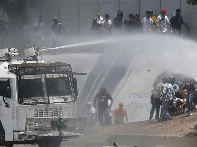 A Bolivarian National Guard water canon sprays opponents of Venezuela's President Nicolas Maduro during anti-government protests in Caracas, Venezuela. Picture: AP