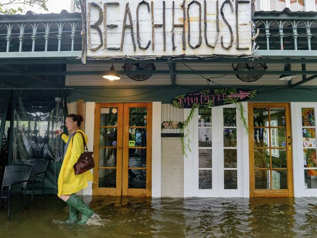 Aimee Cutter, the owner of Beach House restaurant, walks through water surge from Lake Pontchartrain on Lakeshore Drive in Mandeville, Louisiana. Picture: AP