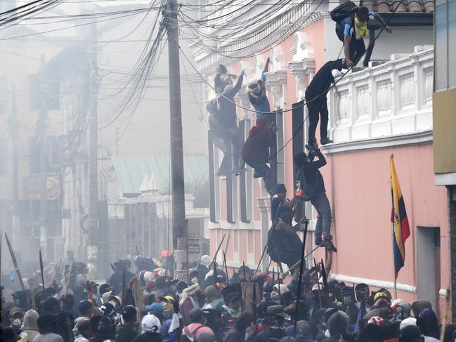 Anti-government demonstrators climb a building during clashes with police in Quito, Ecuador, Friday, Oct. 11, 2019. Protests, which began when President Lenin Moreno's decision to cut subsidies led to a sharp increase in fuel prices, have persisted for days. (AP Photo/Dolores Ochoa)