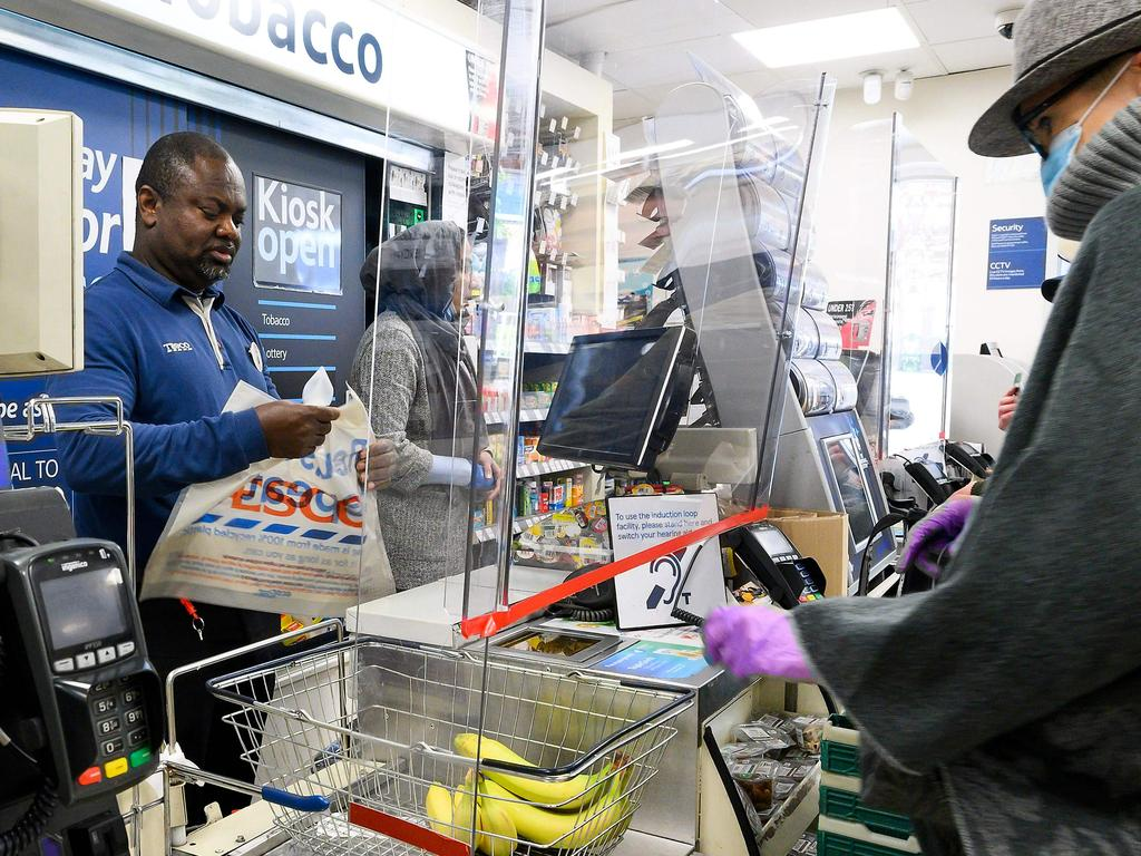 A cashier at a supermarket works behind a protective perspex barrier in London. Picture: AFP