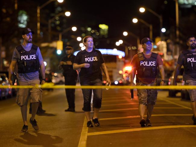 Plain clothes police officers work the scene of shooting in Toronto. Picture: AP