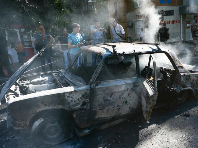 Fatal attack ... local residents look at a burned car where three people died when hit by shelling in the town of Donetsk, eastern Ukraine, on Wednesday.
