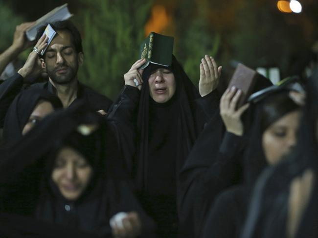 Iranian Shiite Muslims place copies of Koran, Islam's holy book, on their heads while praying during Ramadan on Friday, June 16, 2017. Picture: AP /Vahid Salemi.