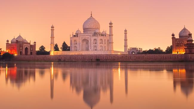 Taj Mahal reflecting in a river on sunset.