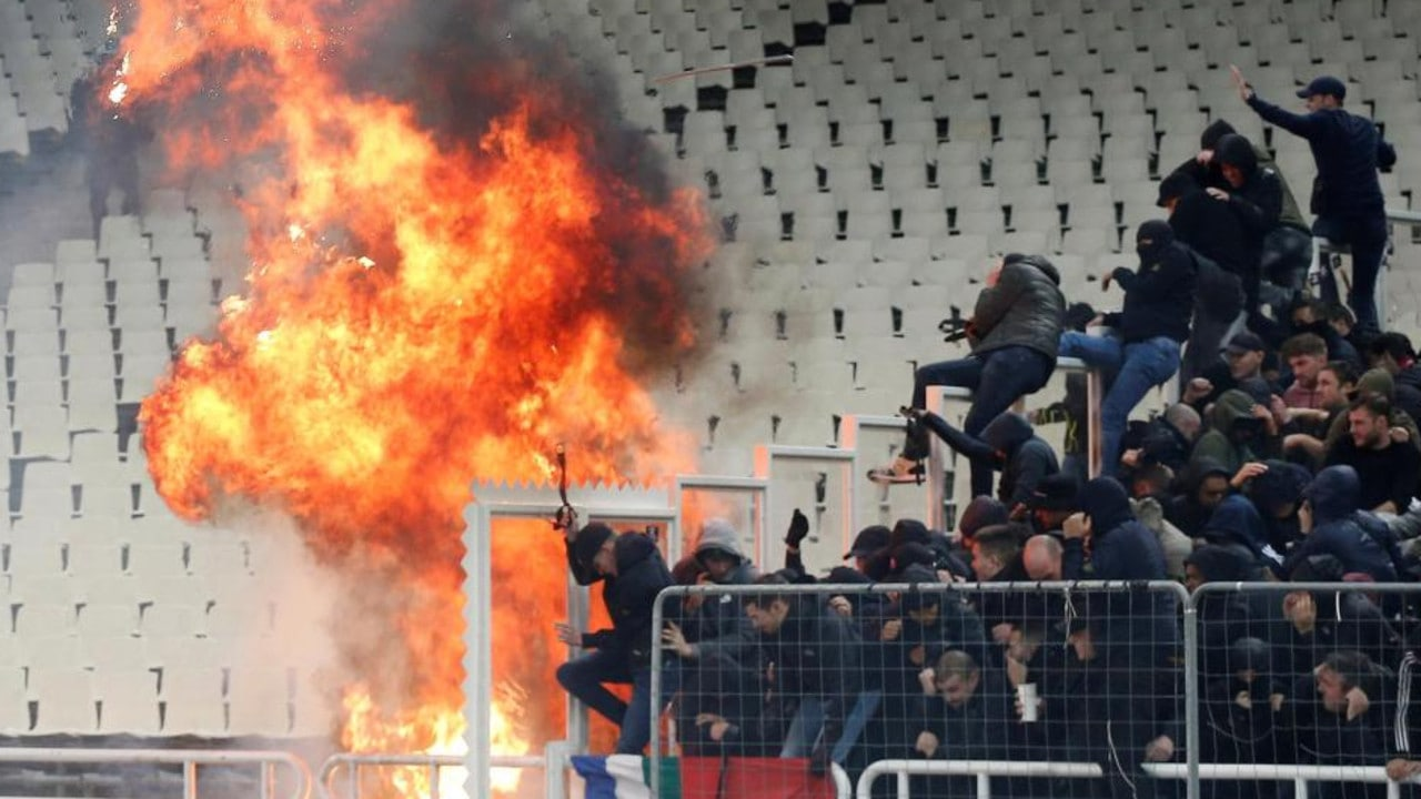 AEK Athens supporters leave Ajax fans bloodied after throwing PETROL BOMB into away end