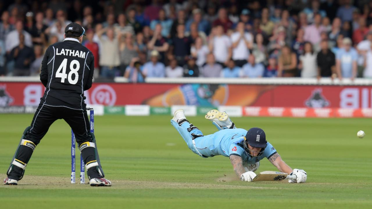 England's Ben Stokes dives to make his ground and the ball hits his bar, going for a boundary.