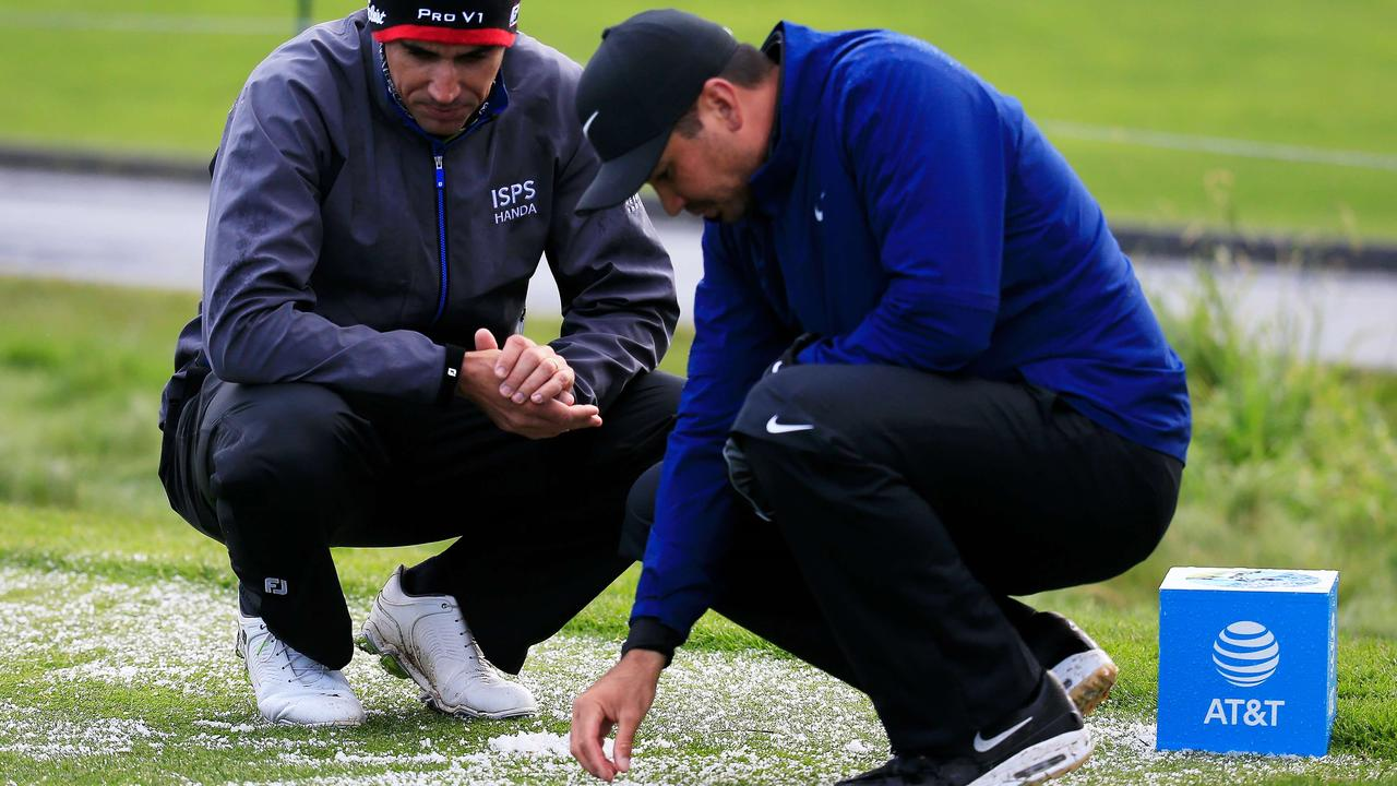 Rafael Cabrera-Bello and Jason Day examine hail on the third tee. Photo: Chris Trotman/Getty Images/AFP