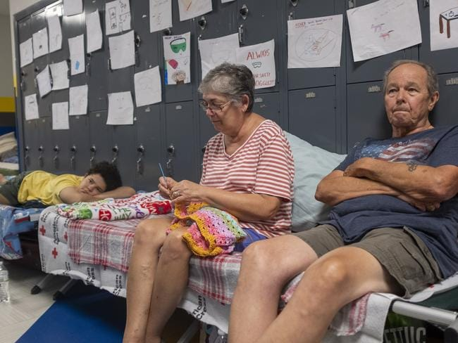 Gordon and Dina Reynolds, with their 11-year-old granddaughter, Abby, sit on cots in the hall way of the North Myrtle Beach High School that is currently being used as a Red Cross evacuation shelter in North Myrtle Beach, South Carolina. Picture: Jason Lee/The Sun News via AP