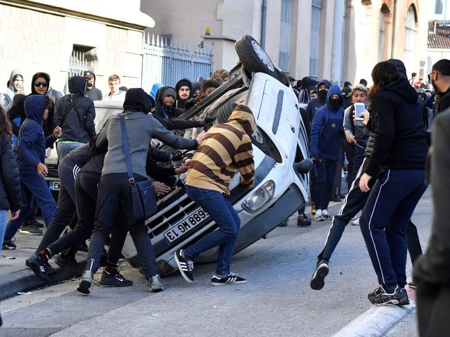 Protesters overturn a vehicle on December 6 in Marseilles, during a demonstration of high school students protesting against French government education reforms. Picture: Gerard Julien/AFP
