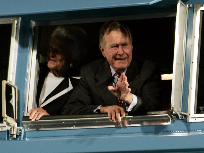 In this Oct. 18, 2005, file photo, former President George H.W. Bush and his wife Barbara wave out the window of a new locomotive numbered 4141 in honor of the 41st president at Texas A&M University in College Station, Texas. The train will carry Bush's remains to his final resting place. Picture: AP