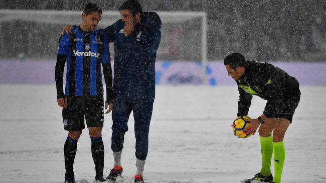 Juventus's Italian goalkeeper Gianluigi Buffon (C) and Atalanta's Brazilian defender Rafael Toloi (L) look on as Italian referee Maurizio Maiani checks the conditions