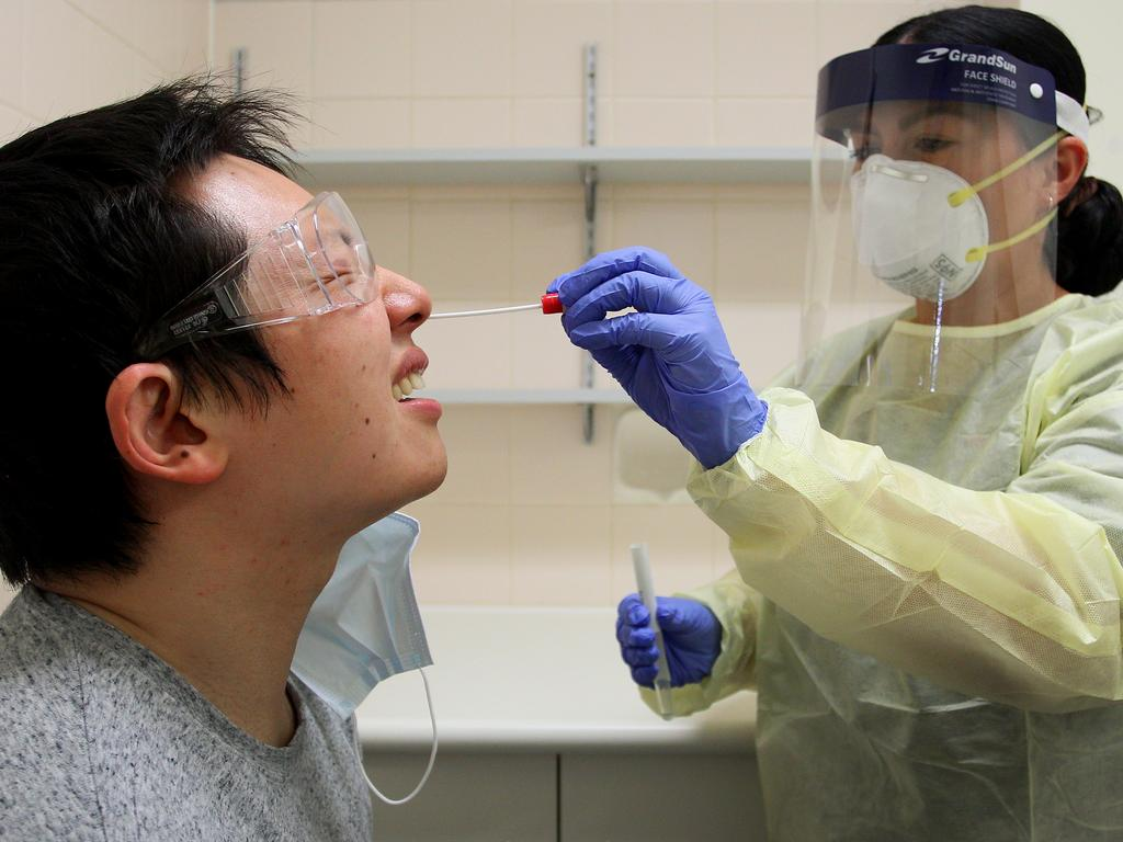 Registered nurse Sharan Coulter conducts a nasal swab test on Shi Yang Liu in the clinical assessment room at St George Hospital. Picture: Getty Images