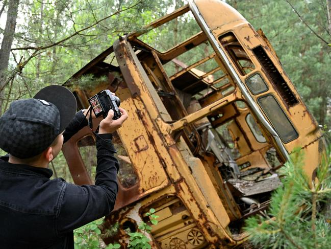 A visitor takes a picture of the wreckage of a bus in the ghost city of Pripyat during a tour in the Chernobyl exclusion zone. Picture: Genya Savilov/AFP