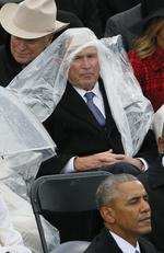 Former President George W. Bush keeps covered under the rain during the inauguration ceremonies swearing in Donald Trump as the 45th president of the United States on the West front of the U.S. Capitol in Washington, U.S on January 20, 2017. Picture: Reuters